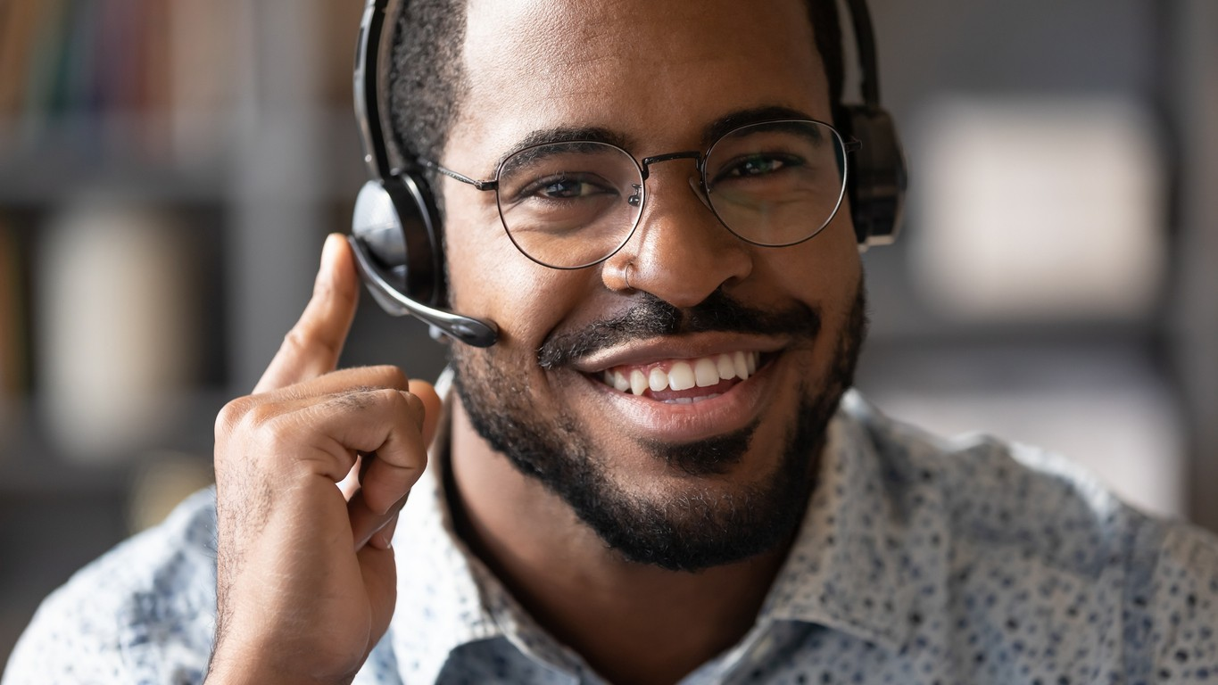 Closeup african man wear headset with microphone look at camera